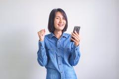 Азиатская девушка с голубым телефоном удерживания руки левой стороны рубашки стоковая фотография rf