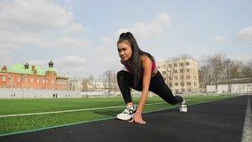 Азиатская девушка youn спортсмена готовая для начала на стадионе спорта сток-видео