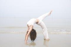 Азиатская девушка выполняя йогу на пляже Стоковое фото RF