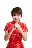 Азиатская девушка в китайском платье cheongsam с жестом congratula Стоковая Фотография
