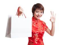 Азиатская девушка в китайском платье cheongsam с хозяйственной сумкой стоковые изображения