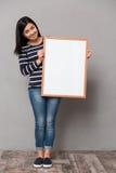 Азиатская девушка держа белую рамку стоковые изображения