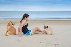 Азиатская девушка женщины играя с собакой 2 на пляже, мопсе и Retriever Лабрадора Стоковое Фото