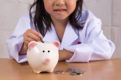 Азиатская девушка играя как деньги баланса доктора в копилке Стоковое Фото