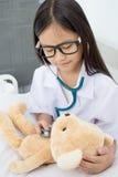 Азиатская девушка играя как доктор Стоковые Изображения