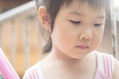 Азиатская девушка играя на спортивной площадке и конце она глаза Стоковая Фотография RF