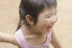 Азиатская девушка играя на спортивной площадке Стоковые Изображения