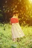 Азиатская девушка играя с пузырями мыла на предпосылке природы переплюните Стоковые Изображения