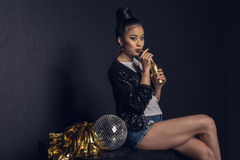Азиатская девушка диско при золотые бутылка, шарик диско и pom-pom представляя и смотря камеру Стоковые Изображения RF