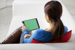 Азиатская девушка используя прибор сенсорной панели Стоковые Фото