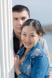 Азиатская девушка и европейский парень представляя близко столбца outdoors Стоковое Изображение RF