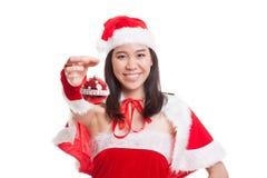 Азиатская девушка Клаус Санта Клауса рождества одевает с шариком безделушки Стоковая Фотография