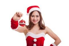 Азиатская девушка Клаус Санта Клауса рождества одевает с шариком безделушки Стоковые Фото