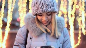 Азиатская девушка печатает на вашем smartphone Предпосылка желтых гирлянд Усмехаться, счастливый, красивый сток-видео
