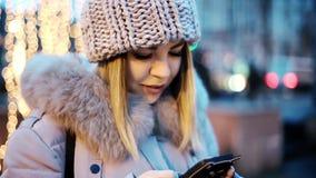 Азиатская девушка печатает на вашем smartphone Предпосылка желтых гирлянд Усмехаться, счастливый, красивый акции видеоматериалы
