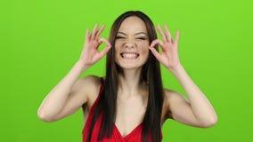 Азиатская девушка представляя в камере и ей усмехаясь зеленый экран движение медленное видеоматериал