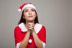 Азиатская девушка рождества с одеждами Санта Клауса молит стоковая фотография rf