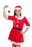 Азиатская девушка рождества с Санта Клаусом одевает с шариком безделушки Стоковая Фотография RF