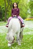 Азиатская девушка сидя на пони Стоковое Фото