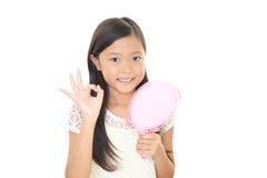 Азиатская девушка смотря ее сторону в зеркале Стоковое фото RF