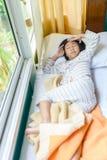 Азиатская девушка спать на кровати покрытой с одеялом Стоковые Фото