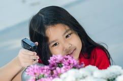 Азиатская девушка с застенчивой улыбкой и милым цветком Стоковые Изображения