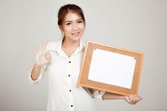 Азиатская девушка с штырем чистого листа бумаги на пробковой доске Стоковое Изображение RF