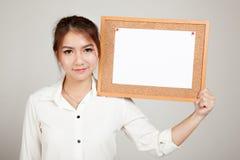 Азиатская девушка с штырем чистого листа бумаги на пробковой доске Стоковые Изображения