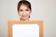 Азиатская девушка с штырем чистого листа бумаги на пробковой доске Стоковые Изображения RF