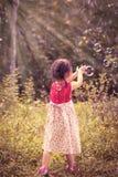 Азиатская девушка улавливает пузыри мыла на предпосылке природы outdoors Стоковые Фотографии RF