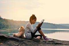 Азиатская девушка читая книгу с плюшевым медвежонком на природе, одна девушка, Стоковые Фотографии RF