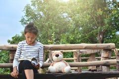 Азиатская девушка читая книгу с плюшевым медвежонком на природе, одна девушка, Стоковое Изображение