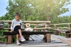 Азиатская девушка читая книгу с плюшевым медвежонком на природе, одна девушка, Стоковые Изображения