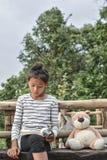 Азиатская девушка читая книгу с плюшевым медвежонком на природе, одна девушка, Стоковая Фотография RF