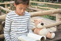 Азиатская девушка читая книгу с плюшевым медвежонком на природе, одна девушка, Стоковое фото RF