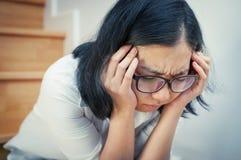 Азиатская девушка eyeglasses утомлянная от ее работы Стоковые Фото