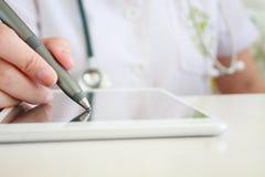 Азиатская женская рука доктора писать цифровой рецепт на таблетке Стоковое фото RF