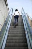 Азиатская женщина бежать на лестницах эскалатора Стоковая Фотография RF