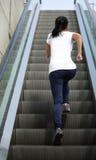 Азиатская женщина бежать на лестницах эскалатора Стоковые Фото