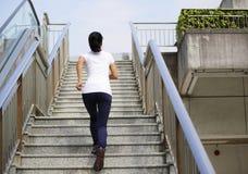 Азиатская женщина бежать на лестницах Стоковые Изображения