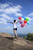 Азиатская женщина бежать на утесе горного пика с покрашенными воздушными шарами Стоковое Изображение
