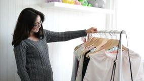 Азиатская женщина выбирая одежды от шкафа дома акции видеоматериалы