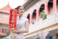 Азиатская женщина в китайце одевает держать двустишие 'приносящий деьги' (c Стоковое фото RF