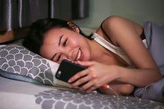 Азиатская женщина в кровати и игре мобильного телефона стоковая фотография
