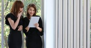 Азиатская женщина 2 в черном платье, используя планшет акции видеоматериалы