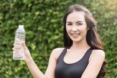 Азиатская женщина в sportswear держа бутылку воды на естественном bac Стоковые Изображения RF