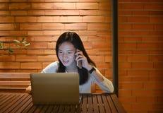 Азиатская женщина говоря на компьтер-книжке телефона на ноче, работать работа Стоковое Изображение RF