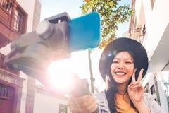 Азиатская женщина делая видео- блог с карданным подвесом смартфона на открытом воздухе - счастливое азиатское influencer имея пот стоковая фотография rf