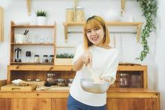 Азиатская женщина делая здоровую еду стоя счастливый усмехаться в кухне подготавливая салат Красивая жизнерадостная азиатская мол Стоковые Фотографии RF