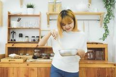 Азиатская женщина делая здоровую еду стоя счастливый усмехаться в кухне подготавливая салат Стоковая Фотография RF